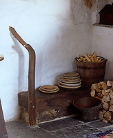 Logs and kindling are stacked beside the range in the living area against a wall coated in lime plaster