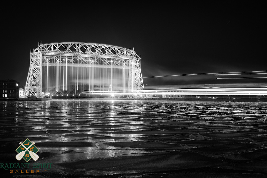 The Philip R. Clarke (767') arrived in Duluth's harbor early in the morning. This long exposure photograph captures the light trails both on the Aerial Lift Bridge and of the vessel entering the harbor. Thick plates of ice cover the foreground like massive puzzle pieces.