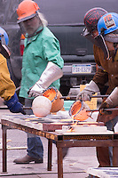 Students and artists work down the line to fill molds with molten iron.