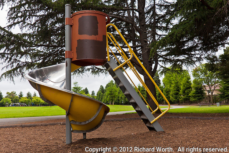 A yellow and red spiral playground slide under a green tree with green grass in the background.