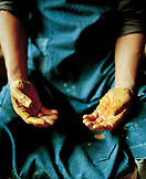 JAPAN, Kyushu, midsection of potter and hands covered in clay