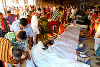 Relatives gather next to the bodies of some of the hundreds of workers killed in the collapsed Rana Plaza complex which are lined up on the floor, covered with white sheeting. The 8 storey building, which housed a number of garment factories employing over 3,000 workers, collapsed on 24 April 2013. By 29 April, at least 380 were known to have died while hundreds remained missing. Workers who were worried about going to work in the building when they noticed cracks in the walls were told not to worry by the building's owner, Mohammed Sohel Rana, who is a member of the ruling Awami League's youth front. He fled his home and tried to escape to neighbouring India after the building collapsed but was caught by police and brought back to Dhaka. Some of the factories working in the Rana Plaza building produce cheap clothes for various European retailers including Primark in the UK and Mango, a Spanish label. . /Felix Features