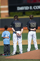 A young baseball player joins Will Craig (22) and Drew Loepprich (23) of the Wake Forest Demon Deacons on the field for the National Anthem prior to the game against the Florida State Seminoles at David F. Couch Ballpark on April 16, 2016 in Winston-Salem, North Carolina.  The Seminoles defeated the Demon Deacons 13-8.  (Brian Westerholt/Four Seam Images)