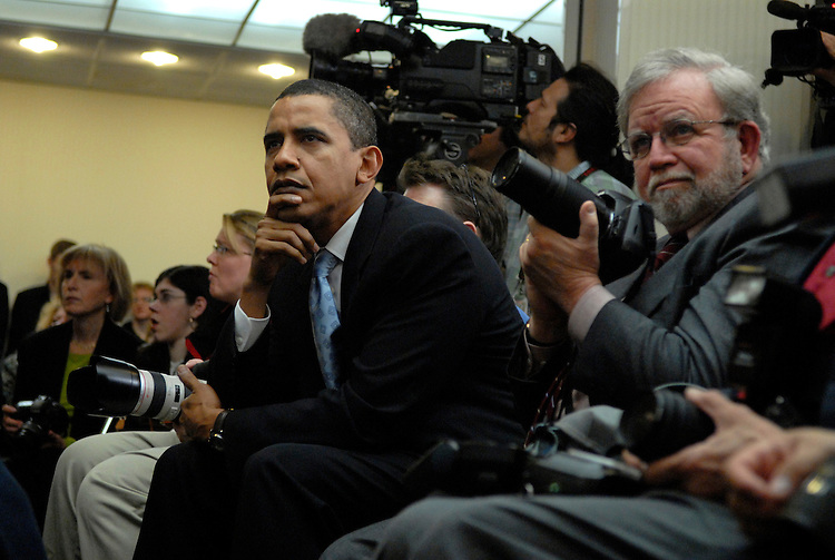 "Sen. Barack Obama, D-Ill., watches a film made by actor George Clooney and his father at the National Press Club at ""SAVE DARFUR: Rally to Stop Genocide.""  Sam Brownback, R-Kan., and Clooney, also appeared."