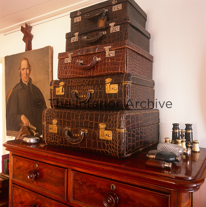 A stack of snakeskin suitcases are arranged on the top of a Victorian chest of drawers. Antique binoculars and hip flaskes are placed on one side.