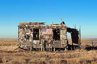 Ruined and abondoned shack with American flag and Christmas wreath.