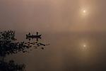 Sunrise in fog on Lake Cassidy Snohomish County two fishermen in small boat silhouetted fishing Washington State USA