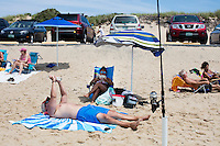 Ian and Liz Towle (center, from front) read on the beach near cars at Herring Cove Beach in the Cape Cod National Seashore outside of Provincetown, Mass., USA, on Fri., July 1, 2016. Portions of the parking lot have been closed after land eroded during storms earlier this year. Ian has a piece of eroded asphalt weighing down a corner of his beach blanket.