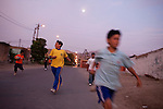 Children run down the street on Tuesday, Apr. 7, 2009 in Ventanilla, Peru.