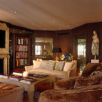 Large wall panels made with antique mirrors reflect the light around this comfortable drawing room