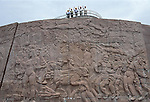 A group of Chinese men in hard hats wave atop a wall of carved figures in Zigui China