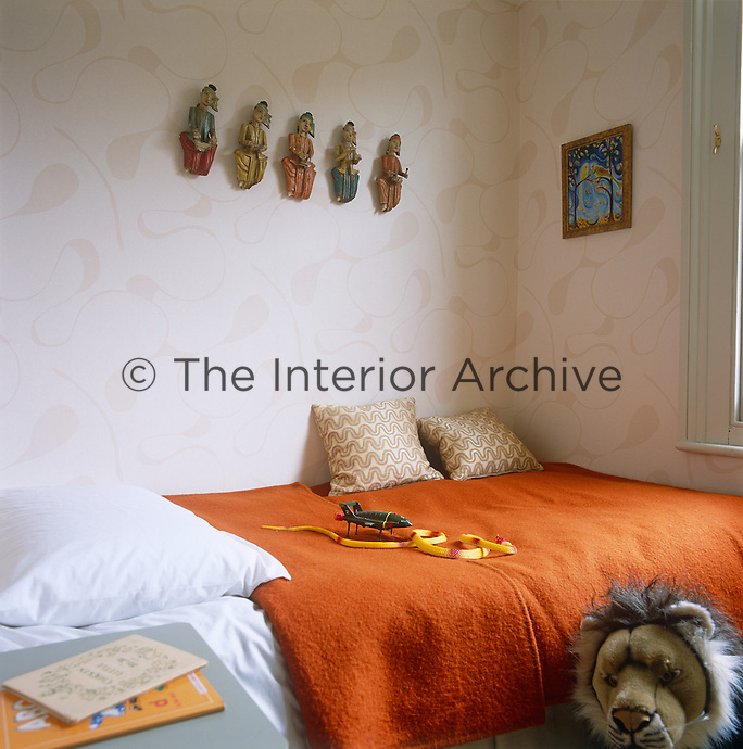 In this child's bedroom five carved musicians look down from the wall on to a bed covered in a vibrant orange blanket