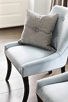 A pair of pale blue chairs in the kitchen, upholstered with studded decoration