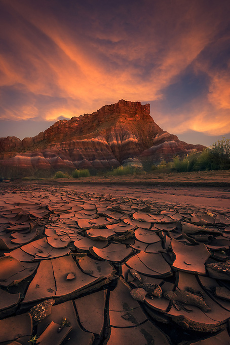 The delicate ground reflects the last light of day beneath the colorful layers of the Utah desert at sunset.