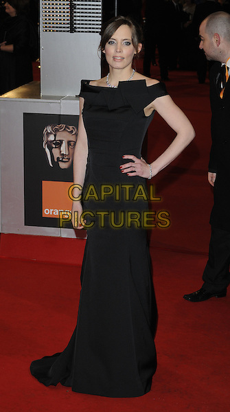 GUEST .Arrivals at the Orange British Academy Film Awards 2010 at the Royal Opera House, Covent Garden, London, England, UK, .21st February 2010.BAFTA BAFTAs full length black long maxi dress hand on hip.CAP/CAN.©Can Nguyen/Capital Pictures