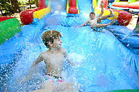 NWA Democrat-Gazette/DAVID GOTTSCHALK  Nash Winters (left), 8, races Rowe Epps, 8, Tuesday, June 5, 2018, as they race down the water slide during the Kanakuk KampOut!  at Mount Sequoyah in Fayetteville. The camp offers five days of faith-based, day camp activities to children from kindergarten through fifth grade. The activities included a zip line, inflatables as well as worship time and small group time with counselors.