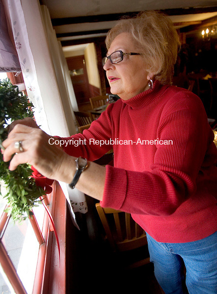 WOODBURY CT. 02 December 2014-120214SV02-Priscilla Steponaitis puts a wreath on a window of the Curtis House Inn while decorating for the holidays in Woodbury Tuesday. The Curtis House will host a wine tasting fundraiser on Dec. 12 from 5-7:30pm. The event is sponsored by the Woman&rsquo;s Club of Woodbury.<br /> Steven Valenti Republican-American