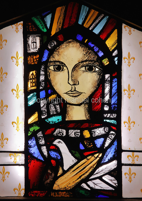 Stained glass window of St Joan of Arc holding a dove, by Greg Tricker, 2013, in the exhibition 'Lumiere Divine', in the Cathedrale Notre-Dame de Reims or Reims Cathedral, Reims, Champagne-Ardenne, France. The cathedral was built 1211-75 in French Gothic style with work continuing into the 14th century, and was listed as a UNESCO World Heritage Site in 1991. Picture by Manuel Cohen