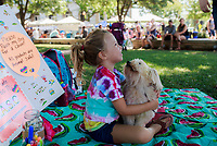 NWA Democrat-Gazette/CHARLIE KAIJO Reese MacLeod of Fayetteville hugs her dog &quot;Little White Dog&quot; during the farmer's market, Saturday, July 7, 2018 at the Square in Bentonville. She is raising money for the Teen Action Support Center by allowing visitors to paint her dog.<br />
