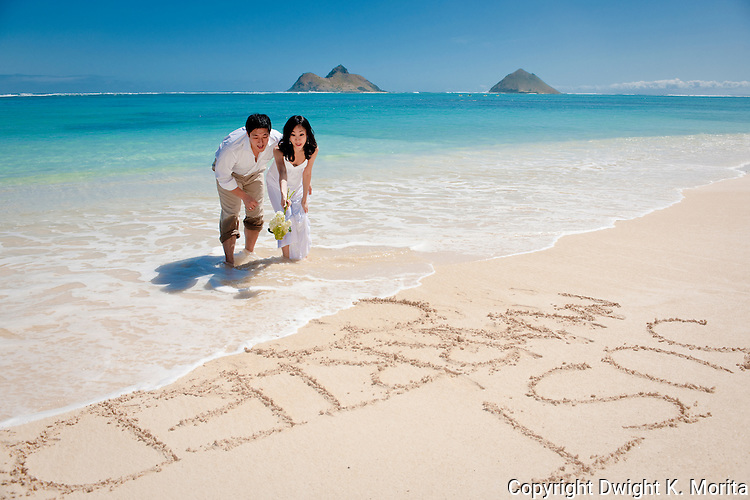 "Asian bride and groom watch a wave erase their ""Just Married"" mark in the sand during a stroll on Lanikai beach."
