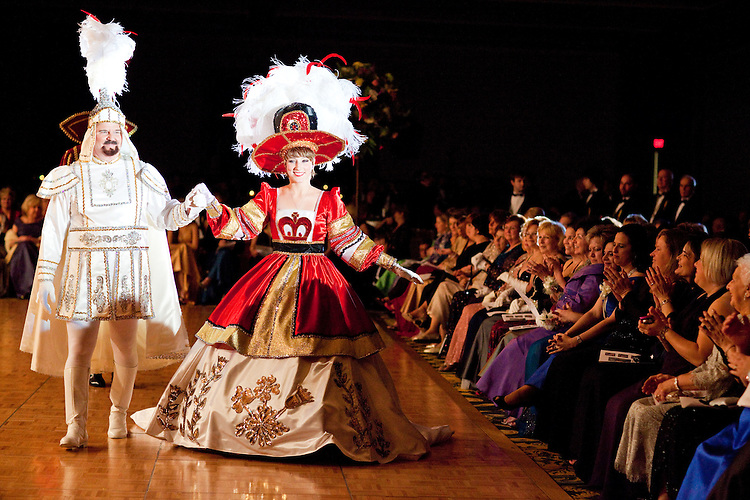 A krewe officer escorts royal maid Margaret Kane around the ballroom at the Krewe of Carrollton's ball in New Orleans on February 5, 2010.