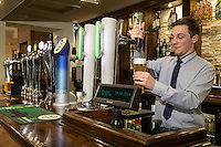 Ben Lovegrove serves a 'Perfect Pint' at The Fountain Bridge carvery restaurant and pub at Kirkby in Ashfield, Nottinghamshire.