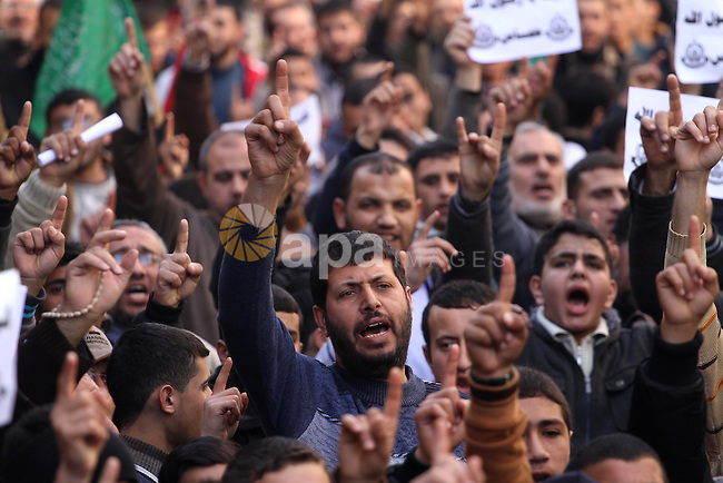 "Palestinians hold placards and shout slogans praising Islam's Prophet Mohammed during a demonstration organised by Islamist movement Hamas against the cover cartoon of the Prophet published by French satirical magazine Charlie Hebdo in Jabalia refugee camp in the northern Gaza Strip on January 23, 2015. Charlie Hebdo has printed cartoons depicting Mohammed, including one on the cover of its ""survivors"" issue published after jihadist gunmen attacked its Paris offices, killing 12 people. Photo by Mohammed Asad"