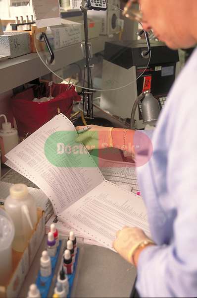 lab technician reading printout of test sample