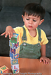 19 month old toddler boy stacking blocks building block tower closeup biracial Native American and Caucasian vertical