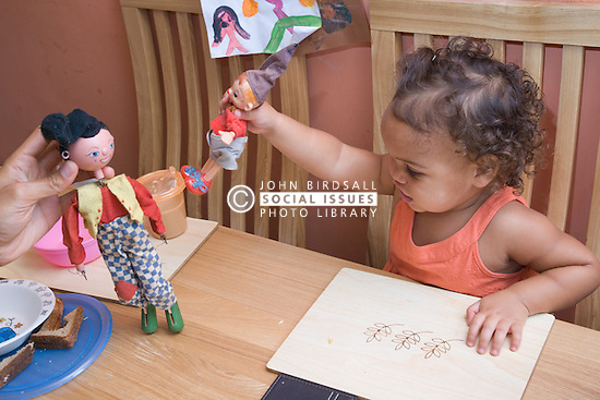 Toddler sitting at the table playing with dolls,