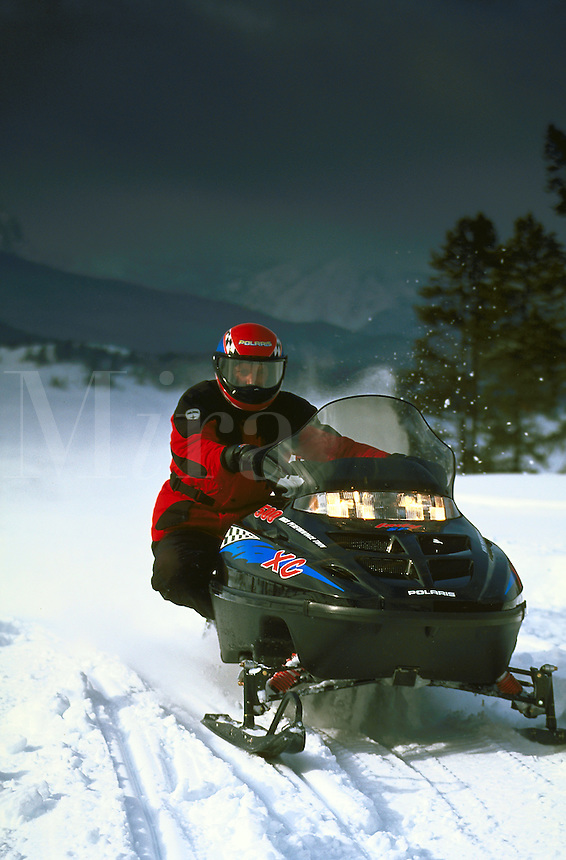 A snowmobile rider drives during dusk in the mountains.