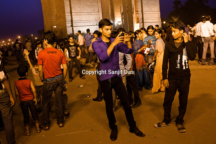 Young Indian take photos of each other using mobile phones near India Gate in New Delhi, India  Photograph: Sanjit Das/Panos