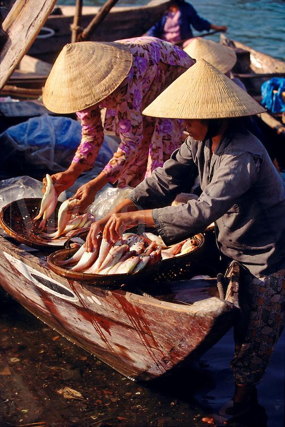 Shoppers and vendors at morning fish market Hoi An Vietnam.