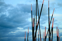coral bamboo like metal poles installation against a vivid blue sky