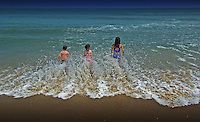 Children sand in surf as it washes over their feet at the beach