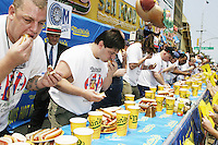 Eaters stuff as many much as possible into their mouths at the infamous I.F.O.C.E. sanctioned Nathan's Famous 4th of July hot dog eating competition in 2004.