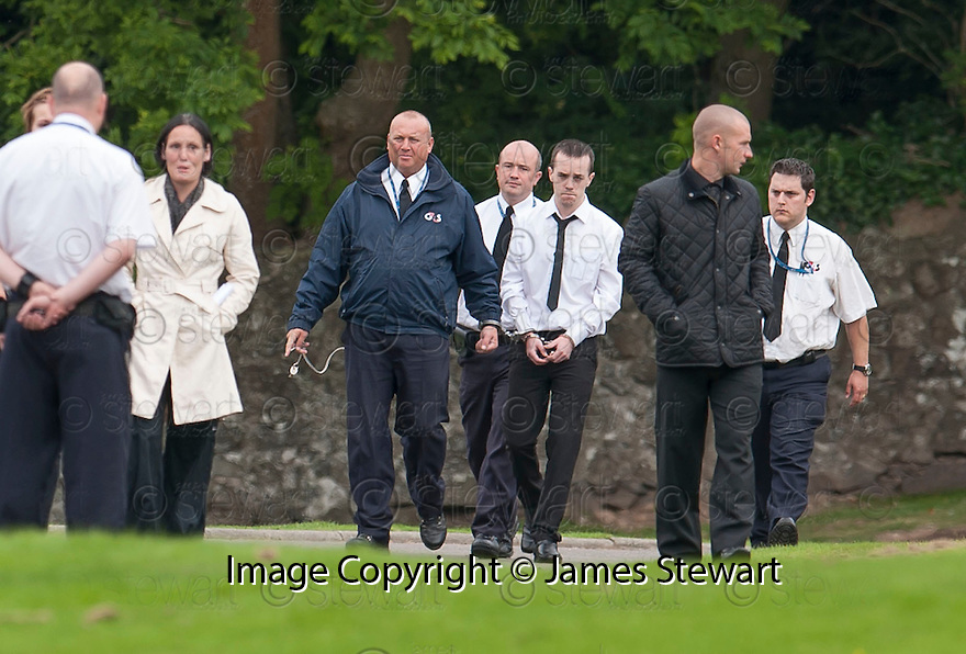 Grandson Kevin Boon is led away, handcuffed to a G4S officer to a van to taken away from the funeral of former crime family matriarch Mags Haney at St Thomas' Cemetery, Cambusbarron.