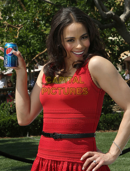 """Paula Patton.Paula Patton Invites Fans To Sample New Pepsi Next For """"Drink It To Believe It"""" Campaign Held at The Grove, Los Angeles, California, USA..April 9th, 2012.half length dress hand on hip red sleeveless can black belt smiling .CAP/ADM/KB.©Kevan Brooks/AdMedia/Capital Pictures."""