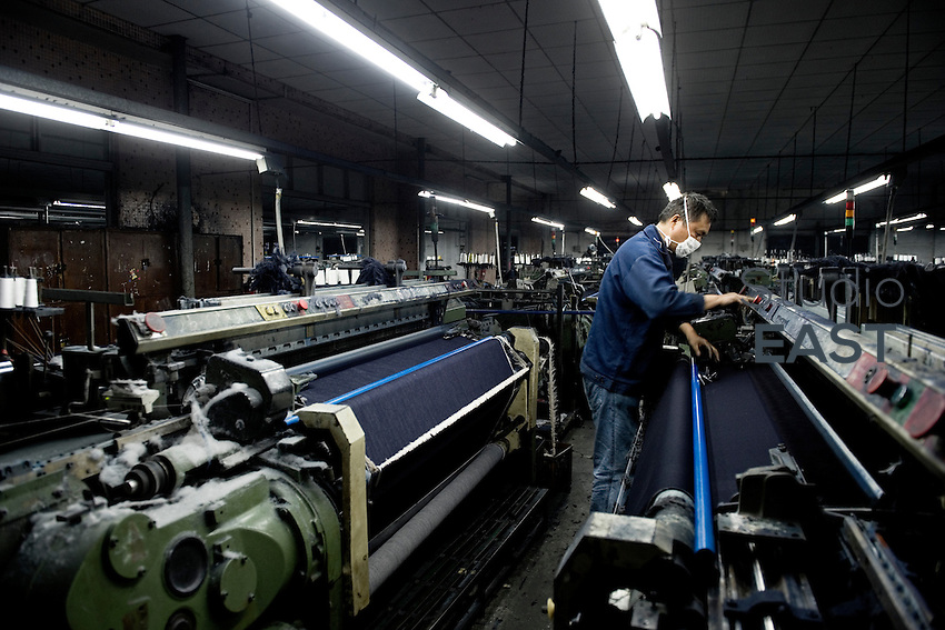 A worker intervenes on a power loom weaving denim to be used to manufacture blue jeans in LSH textile company, in Xintang, Guangdong province, China, on February 9, 2012. Photo by Lucas Schifres/Pictobank