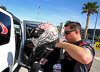 Mar 28, 2014; Las Vegas, NV, USA; Crew member Chris Abbott helps NHRA top fuel dragster driver Steve Torrence adjust his Hans safety device during qualifying for the Summitracing.com Nationals at The Strip at Las Vegas Motor Speedway. Mandatory Credit: Mark J. Rebilas-