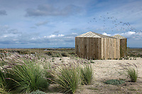 The pair of minimal cabins is built of recycled wood on a pontoon overlooking the estuary
