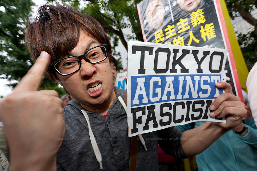 A young Japanese man gives the middle finger sign while holding an anti fascist sign at a protest against the revision of article 9 of the Japanese Constitution outside the Prime-Minister's house in Kasumigasaki, Tokyo, Japan. Monday June 30th 2014. Over 10,000 people showed their support for Japan's unique peace constitution and called on the government to halt its reinterpretation of Article 9 allowing Collect Self Defence which is expected to become law on July 1st