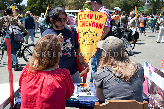 August 15, 2009. Preeti Shekar of Berkeley speaks to volunteers tabling for Justice in Nigeria Now. About two hundred people participated in a rally, march, and demonstration protesting Chevron's Richmond oil refinery renovation and expansion project. The event was organized by Mobilization for Climate Justice-West, a coalition of over thirty organizations, working to bring awareness to the refinery issue as well as the United Nations Climate Change Conference taking place in December in Copenhagen. Event organizers claim that the Richmond refinery project will allow the facility to refine heavier and dirtier crude that will result in more air pollution, greenhouse gas (GHGs) emissions, and health risks. A court ruling recently put the refinery project on hold saying that further environmental impact reporting was needed. Many protesters were also concerned about the environmental and human health impacts of oil company projects outside the United States. Richmond, California, USA