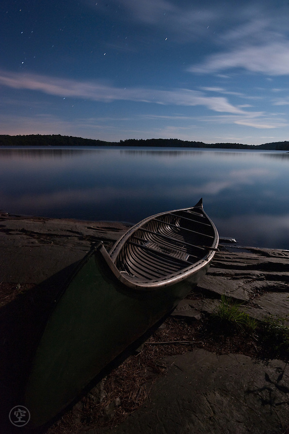 A traditional cedar and canvass Old Town canoe by moonlight and starlight at night on the shore of David Lake, Killarney Provincial Park, Ontario