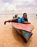 PANAMA, Bocas del Toro, a young boy lies on the front of a fishing boat, Central America