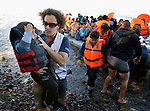 A volunteer carries a boy to safety as a rubber raft lands on a beach near Molyvos, on the Greek island of Lesbos, on October 30, 2015. The boat, which came from Turkey, was filled with refugees who paid Turkish traffickers huge sums for the trip. They were received in Greece by local and international volunteers, then proceeded on their way toward western Europe.