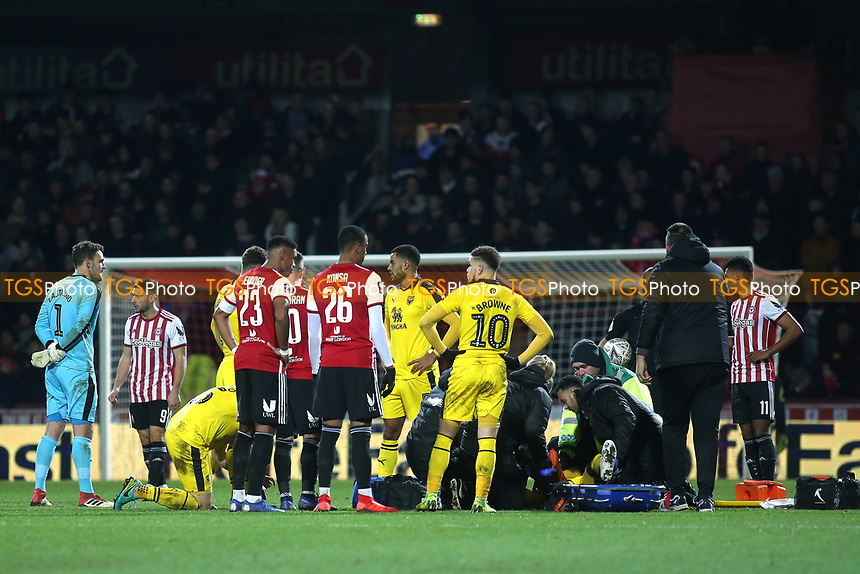 Shandon Baptiste of Oxford United is lifted onto the stretcher by the medical team prior to him being carried off the pitch during Brentford vs Oxford United, Emirates FA Cup Football at Griffin Park on 5th January 2019