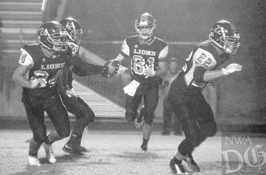 Photo by Randy Moll<br /> Layne Martinez, Gravette senior, prepares to take a handoff from Bryce Moorman while Jordan Burnett and Jackson Soule' block during play against Shiloh Christian on a rainy night, Friday, Oct. 30, 2015, in Lion Stadium.