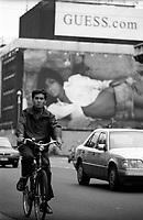 milano, un uomo cinese in bicicletta in corso venezia con alle spalle gli ex Caselli Daziari di Porta Venezia in corso di restauro e coperti da pubblicità --- milan, a chinese man by bicycle on venezia street with the old excise houses on the background temporarily covered with advertising during their restore