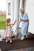 Polish great grandmother and great granddaughter sweeping and mopping porch entry way age 86 and 4. Zawady Central Poland